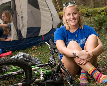 student sitting by tent