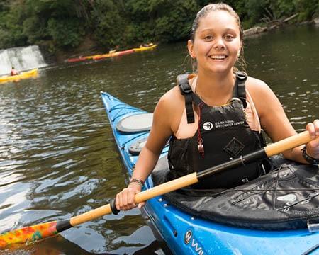 student kayaking near waterfall