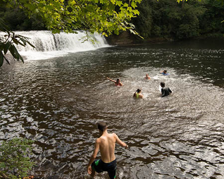 Students swimming by waterfall