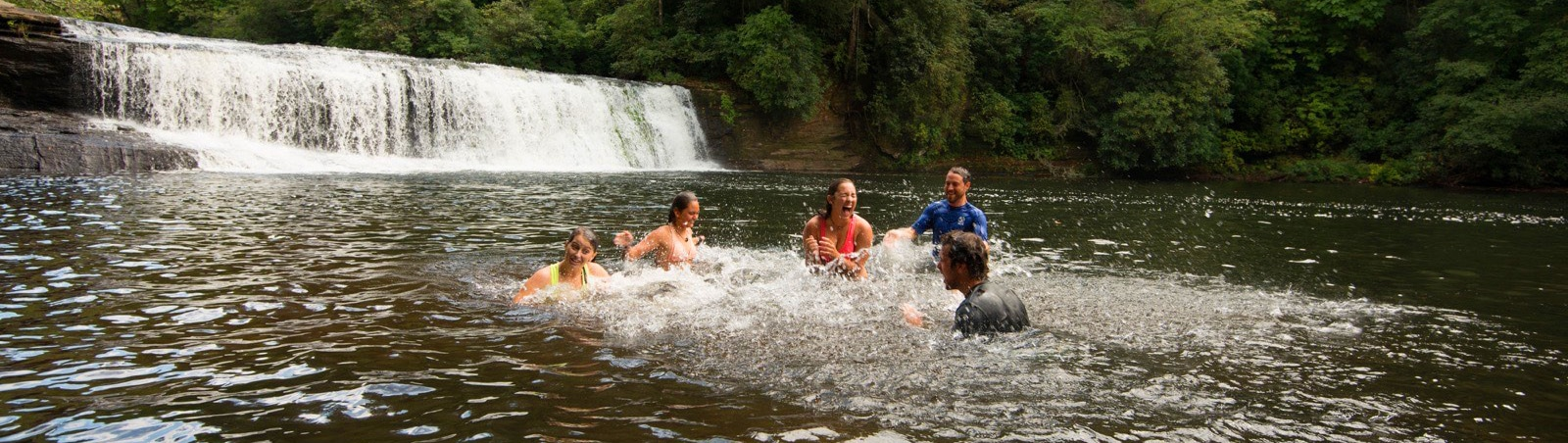 students swimming in front of waterfall
