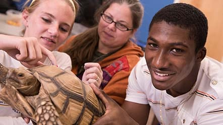students holding turtle