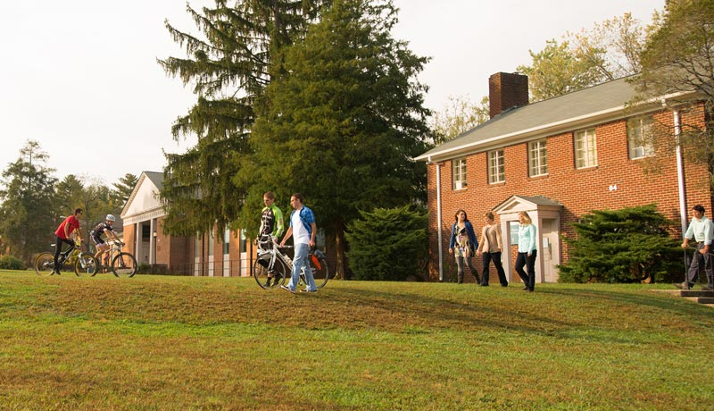Brevard College students walk their bikes over lawn